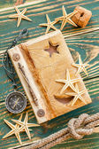 Old notepad with seashells on the deck — Stock Photo