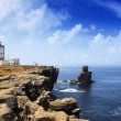 Portuguese lighthouse over blue ocean - Stock Photo