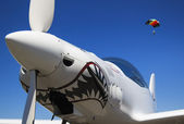 Nose and propeller of a white aeroplane in a blue sky and a parachute — Stock Photo