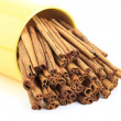 Cinnamon sticks in a yellow cup — Stock Photo