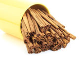 Cinnamon sticks in a yellow cup — Stockfoto