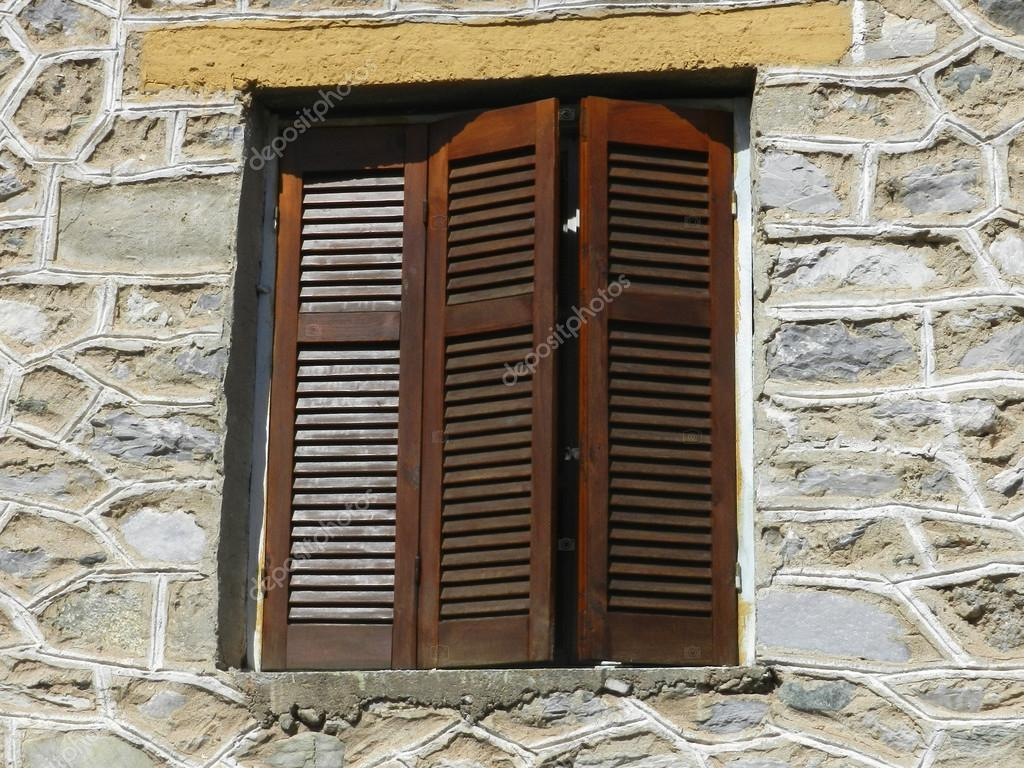 Closed wooden window with shutters on a old stone wall — Stock Photo #13359988