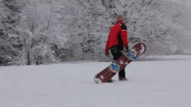 Heavy climbing to the top. Snowboarder gets up the hill after the descent. — Vídeo de stock
