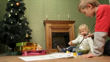 Children paint on canvas. Two small children sitting on the floor and paint a Christmas tree. — Stock Video