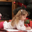 A girl under a Christmas tree waiting to unwrap her presents. Waiting for Christmas. — Stock Video