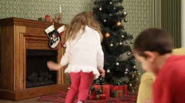 Children search for their presents under a Christmas tree and then hide. Gifts under a Christmas tree. — Stock Video