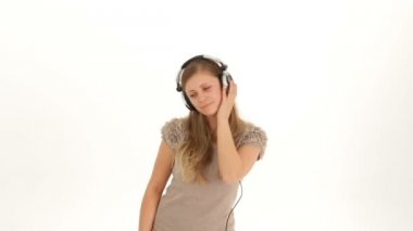 Music in the headphones. A girl in a white shirt and headphones dancing on a white background. Two frames. — Stock Video