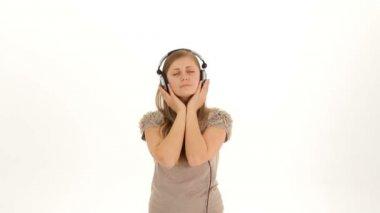 Hudba ve sluchátkách. dívka v bílé košili a sluchátka na bílém pozadí. dva snímky. — Stock video