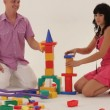 Two adults playing with toy blocks and trying to build a castle. — Stock Video #16933625