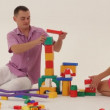Two adults playing with toy blocks and trying to build a castle. — Stock Video #16933649