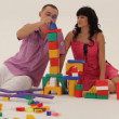 Two adults playing with toy blocks and trying to build a castle. — Stock Video #16933673
