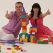 Two adults playing with toy blocks and showing thumb up — Stock Video #16933675