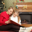 Mother reading a story to her daughter under a Christmas tree. Reading a story. — Stock Video #17686849
