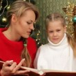 Mother reading a story to her daughter under a Christmas tree. Reading a story. — Stock Video #17687245