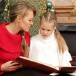 Mother reading a story to her daughter under a Christmas tree. Reading a story. — Stock Video #17687347
