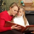 Stock Video: Mother reading story to her daughter under Christmas tree. Reading story.