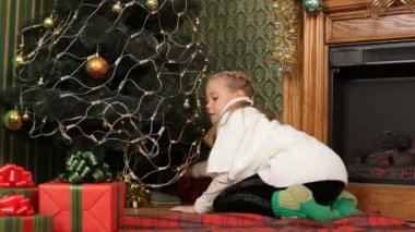 Little girl hiding presents under a Christmas tree. Hiding presents. — Stock Video