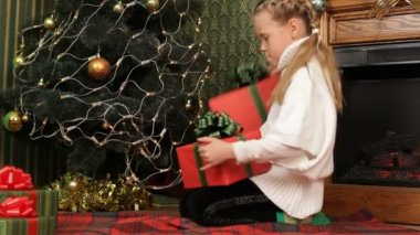 Girl looking through the presents under a Christmas tree. Child and presents. — Stock Video