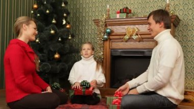 A family seating near a fireplace and exchanging gifts. New Years Eve. — Stock Video