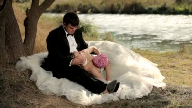Newlyweds on the bank of small river. — Stock Video