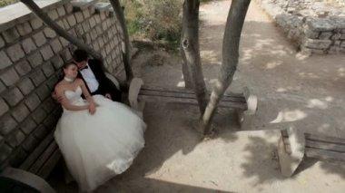Romance v parku. novomanželé sedí na lavičce a objímání. — Stock video