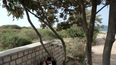 Mladý pár sedící na lavičce v parku. — Stock video