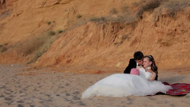 Les nouveaux mariés se détendre sur la plage de sable. — Vidéo