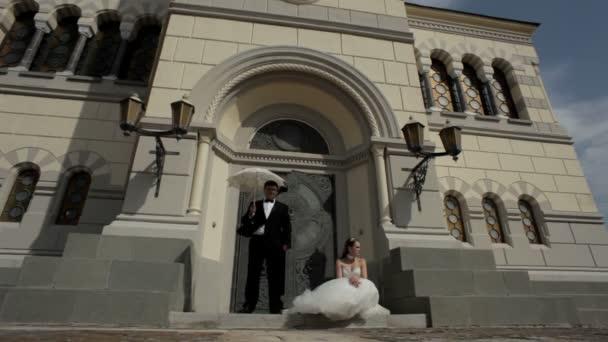 Recién casados en la puerta de la iglesia. — Vídeo de stock