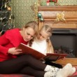Mother reading a story to her daughter under a Christmas tree. Reading a story. — Stock Video #18193767