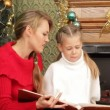 Mother reading a story to her daughter under a Christmas tree. Reading a story. — Stock Video #18194269