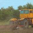 Stock Video: Large farm tractor plowed land. Behind tractor heaves big cloud of dust. Tracking shot.