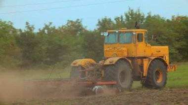 A large farm tractor plowed land. Behind the tractor heaves a big cloud of dust. Tracking shot. — Stock Video