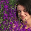 Stock Video: Girl is among purple flowers Young girl lying on beautiful field of purple flowers and smiles.