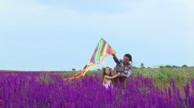 Mother and daughter launch a kite. A woman with a small child running through a field of beautiful flowers and launch a kite. — Stock Video