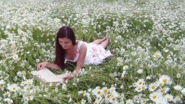 молодая девушка с книгой. молодая девушка сидит на красивое поле ромашки и читать больше книг. — Стоковое видео