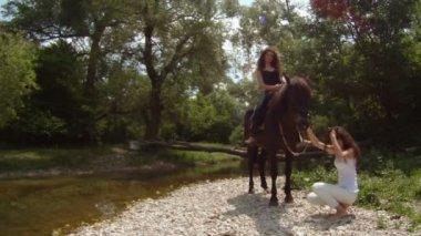 Duas mulheres - um bomnome e o outro ao lado do cavalo. — Vídeo stock