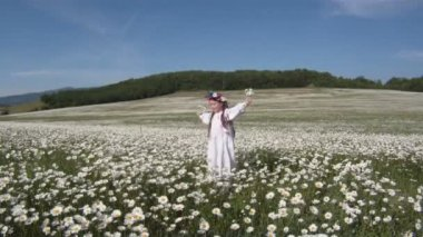Little girl dressed in a traditional Ukrainian costume in a field of daisies. — Stock Video