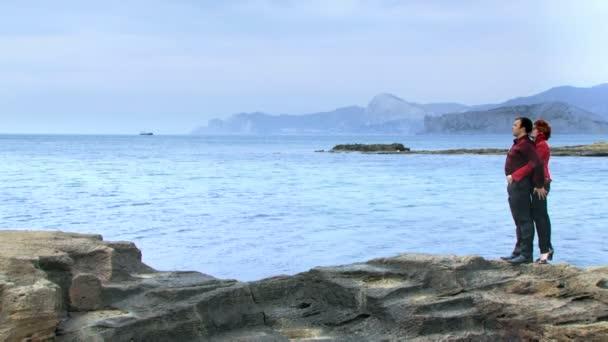 Couple d'amoureux de la mer. un couple d'amoureux, debout sur une falaise près de la mer. — Vidéo