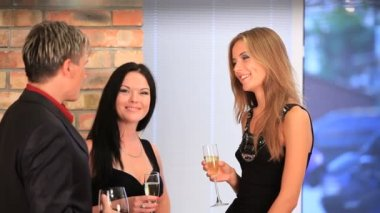 Two women and a man discussing something during a formal party. — Stock Video