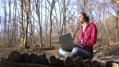Woman finishes work with a laptop. Woman finishes work with a laptop on the background of a beautiful forest. — Stock Video