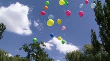 Ballons. plusieurs ballons festifs colorés volent haut dans le ciel — Vidéo