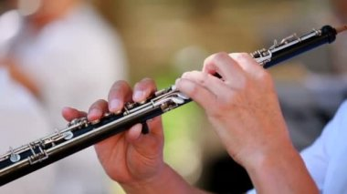 Musician plays the flute. Musicians play the flute professionally. The background is blurred. Close-up. Change of focus from the foreground to the background. — Stok video