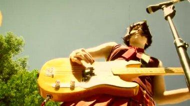 Girl plays bass guitar during an outdoor performance — Stock Video