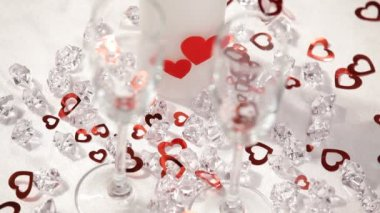 Valentines day theme. HD. Small hearts fall on the wineglasses.Close up. white background. — Stock Video