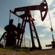 Oil Production. Oil rig extracts resources from the earth. In the background a beautiful blue sky. - Stock Photo