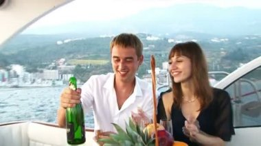 Beautiful couple sitting on the deck of the yacht drinking champagne — Stock Video