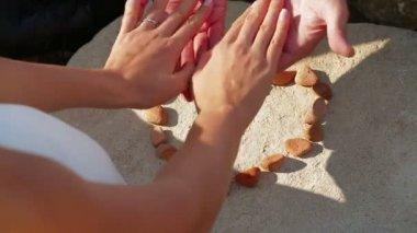 Paar hand in hand in de buurt van een hart gemaakt van kleine stenen. symbool van romantiek. — Stockvideo