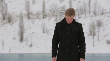 Jonge man wachten iemand in winter park — Stockvideo