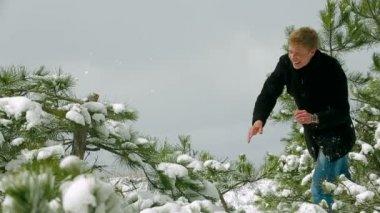 Homem jogando bolas de neve numa floresta de pinheiros — Vídeo Stock