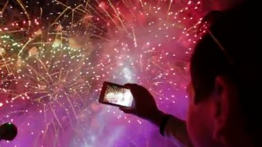 Man filming colorful festive fireworks on camera. Festive fireworks. — Stock Video